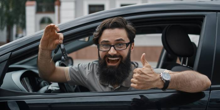 Car dealership, the happiest client. Charismatic man holding car keys showing thumbs up and smiling, with teeth, while sitting in the car looking to camera through the window..